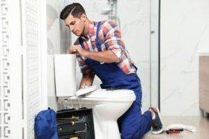 Plumber repairing a toilet cistern with push button in a bathroom