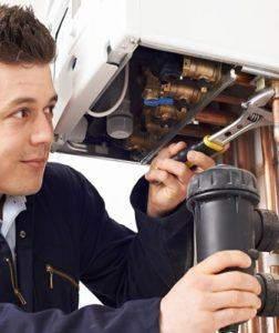 A gas safe registered engineer servicing a gas boiler and magnetite filter