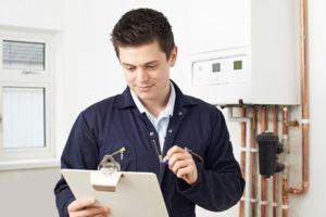 A gas engineer completing paperwork after servicing a gas boiler and safety check