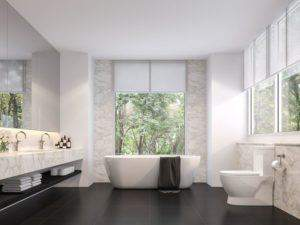 Luxury bathroom with bath tub toilet basin taps and marble tiling