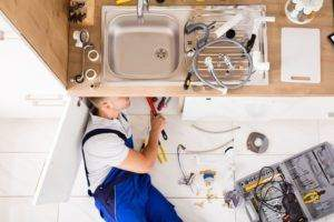 A plumber installing a new kitchen sink and taps